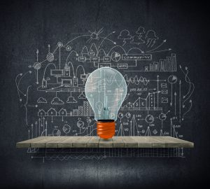 Conceptual image of light bulb on wall with sketches of ideas